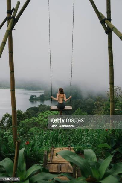 femme sur la balançoire sur la jungle et un lac à bali - bali photos et images de collection