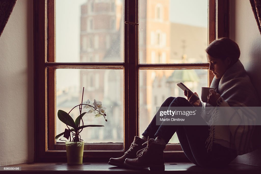 Woman on the window texting : Stock Photo