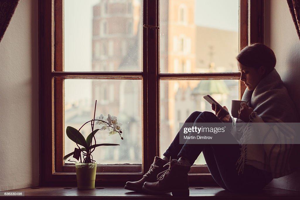 Woman on the window texting : Stockfoto