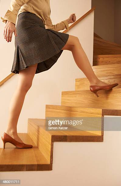 Woman on timber stair making a big step