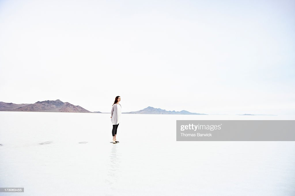 Woman on tip toe at end of stone path in lake : Stock Photo