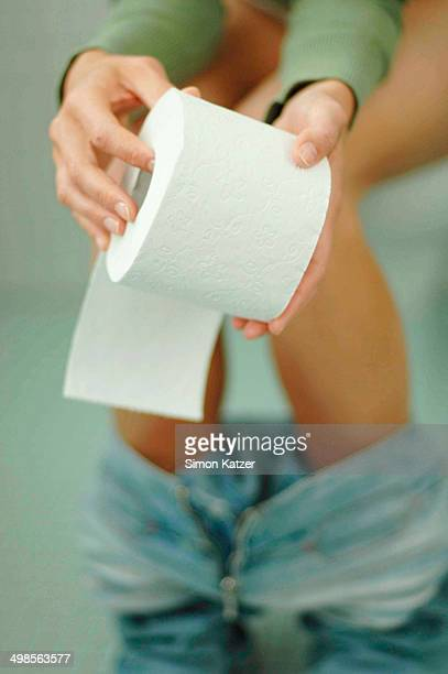Woman on toilet holding spool of toilet paper