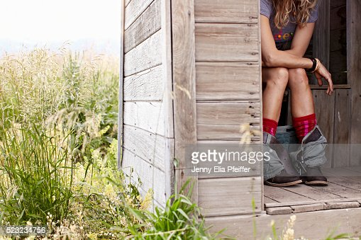 Woman on toilet in outhouse stock photo getty images - How to use the bathroom when constipated ...