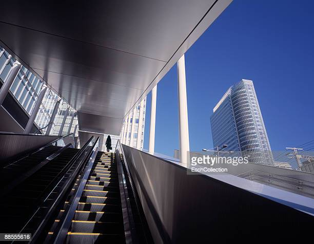 woman on top of a moving elevator in modern tokyo - grand angle photos et images de collection