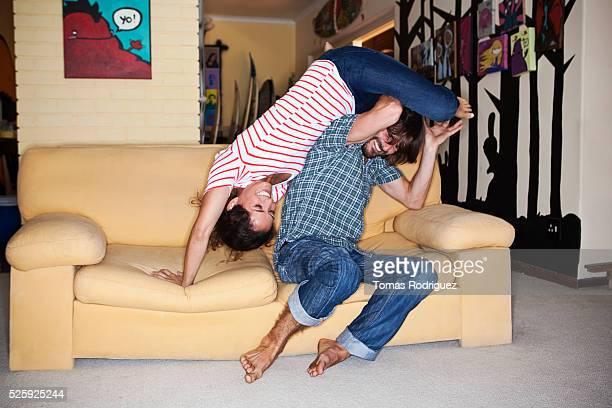 woman on top of boyfriend on sofa - nur erwachsene stock-fotos und bilder