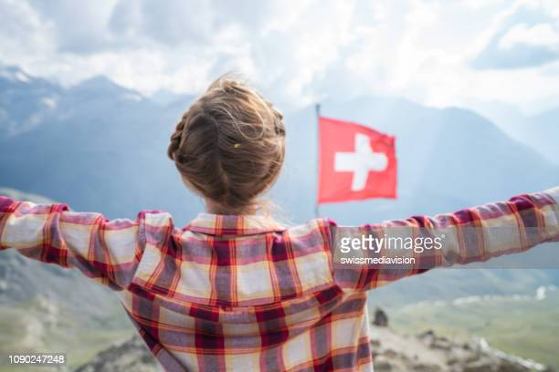 woman on top of the mountain standing arms outstretched; swiss flag in the swiss alps - swiss culture stock pictures, royalty-free photos & images