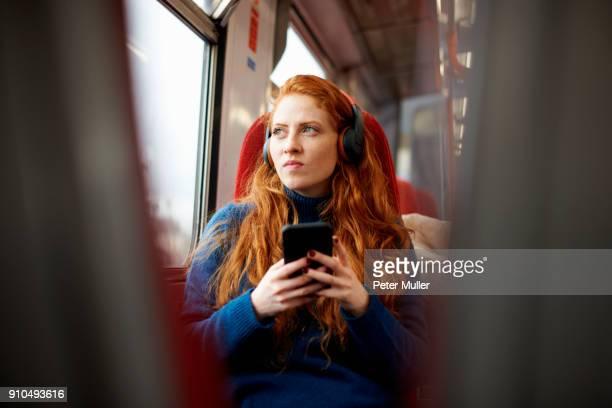 woman on train listening to music on mobile phone with headphones, london - zug stock-fotos und bilder