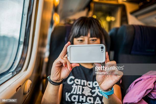 Woman on train using smartphone to take photograph