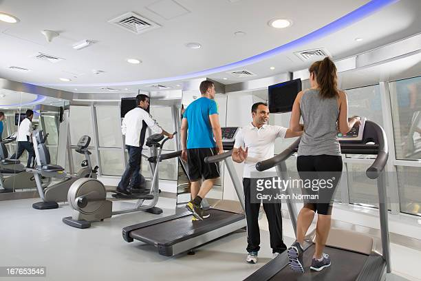woman on treadmill in gym gets advice from trainer