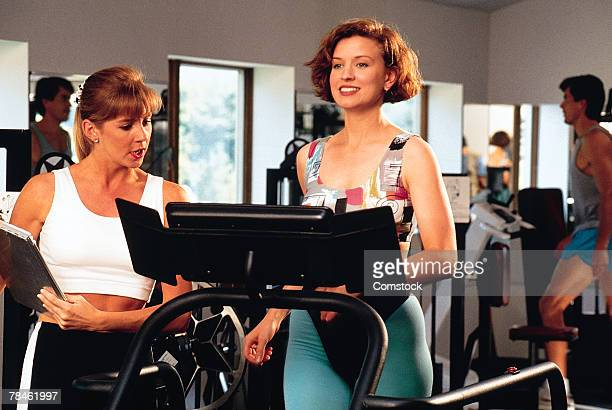 Woman on treadmill in gym with personal trainer