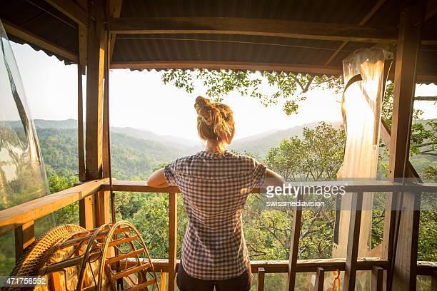Woman on tree house watching sunset