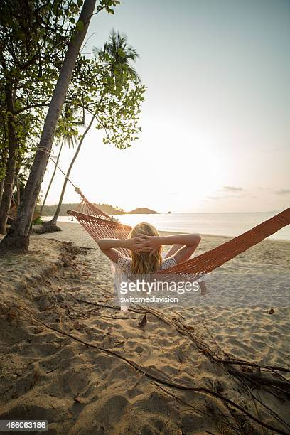 Woman on tropical beach lying down on hammock-Sunset
