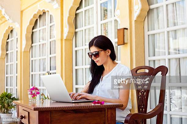 Woman on tropical vacation using laptop in hotel