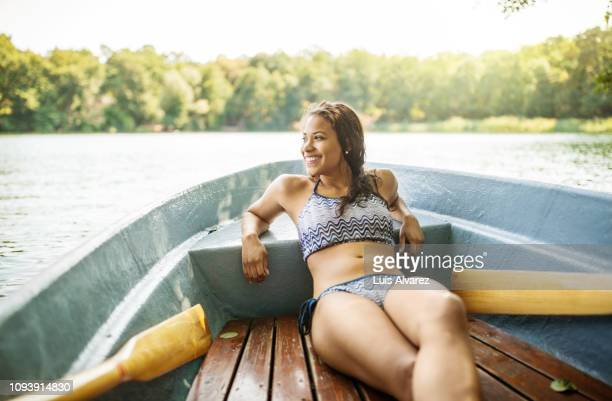 woman on vacation enjoying a boat ride in lake - swimwear stock pictures, royalty-free photos & images