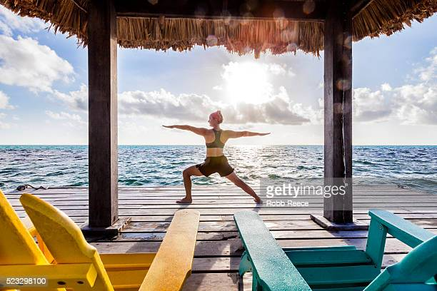 a woman on vacation in belize, doing yoga poses on a dock near the ocean - robb reece stock pictures, royalty-free photos & images