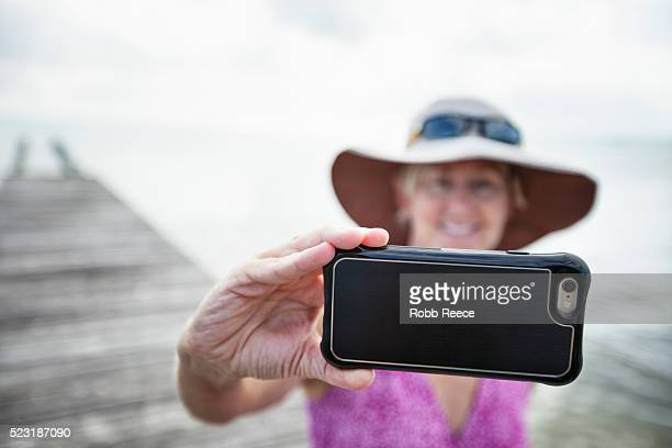 a woman on vacation in belize, photographing herself and the ocean with a smartphone - robb reece stockfoto's en -beelden