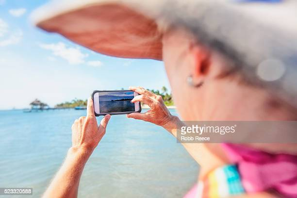 a woman on vacation in belize, photographing the ocean with a smartphone. - robb reece stockfoto's en -beelden