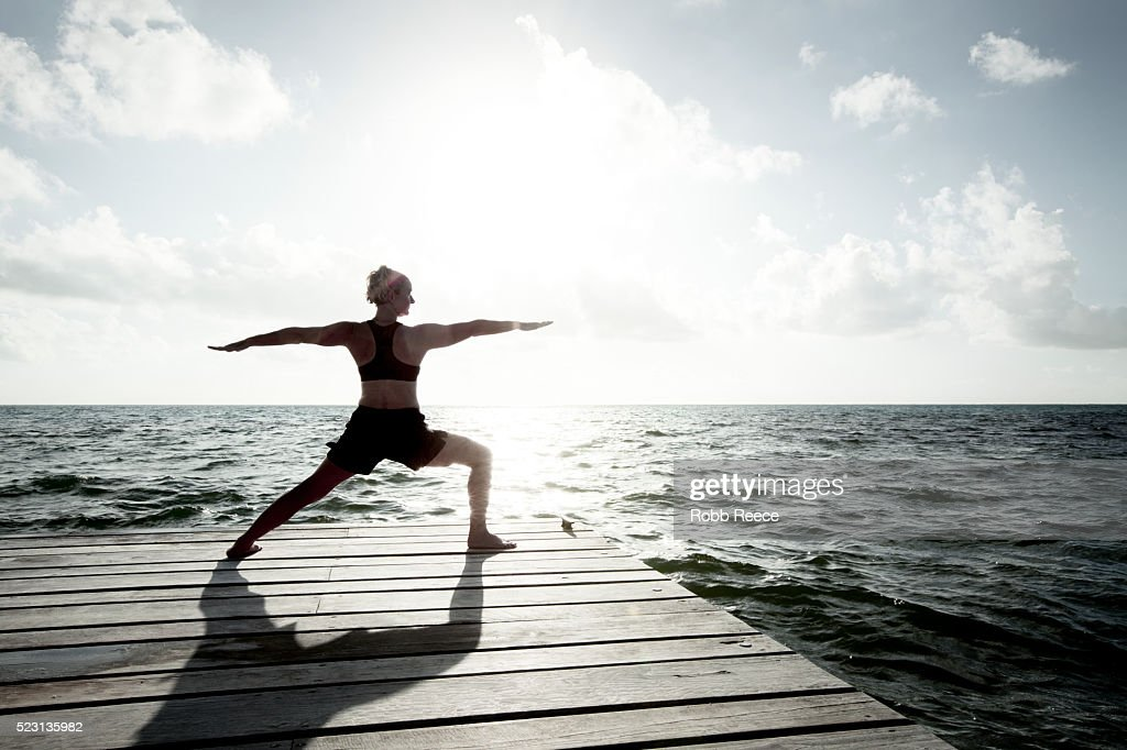 A woman on vacation in Belize, practicing yoga on a dock near the Caribbean Ocean : Stock Photo