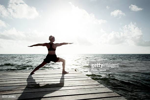 a woman on vacation in belize, practicing yoga on a dock near the caribbean ocean - robb reece stock-fotos und bilder