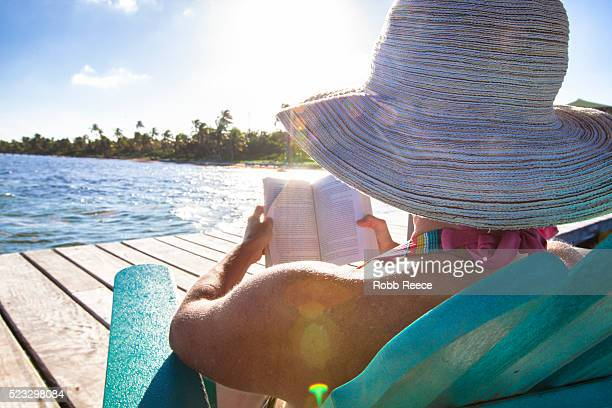 a woman on vacation in belize, sitting by the ocean reading a book - robb reece stock pictures, royalty-free photos & images