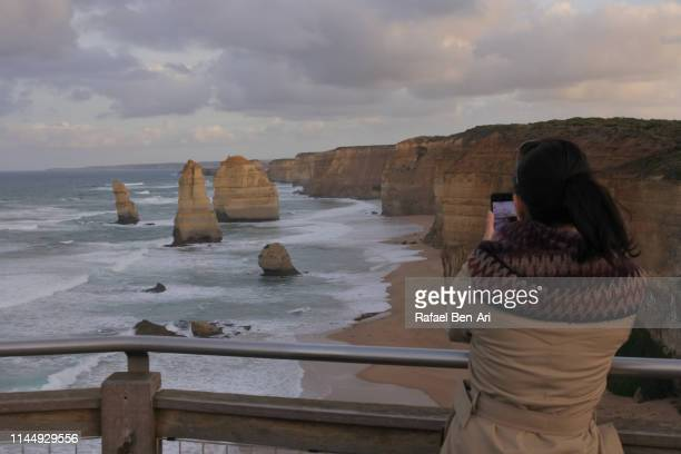 woman on vacation looking at landscape view of the twelve apostles in victoria australia - rafael ben ari stock pictures, royalty-free photos & images