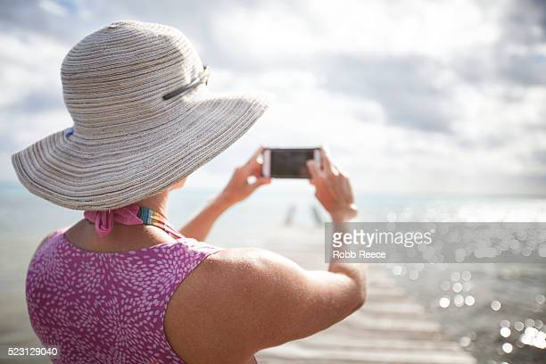 a woman on vacation, photographing the ocean with a smartphone. - robb reece stock-fotos und bilder