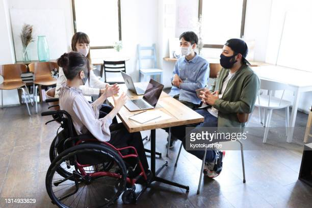 woman on wheelchair with her collegue at office - diversity stock pictures, royalty-free photos & images