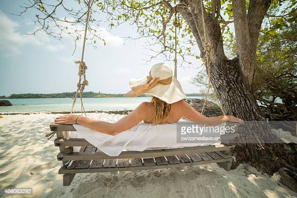Woman on white sand beach sitting on bench hanging