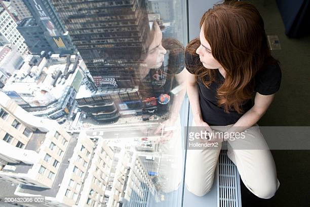 Woman on windowsill overlooking city, elevated view