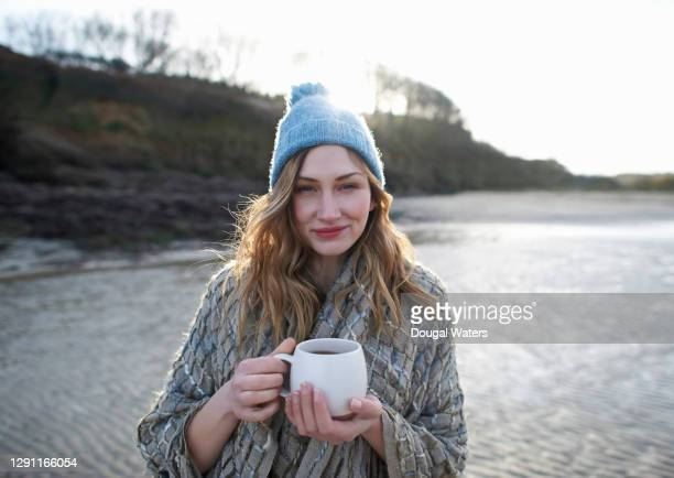 woman on winter beach with hot drink and bobble hat. - one mid adult woman only stock pictures, royalty-free photos & images