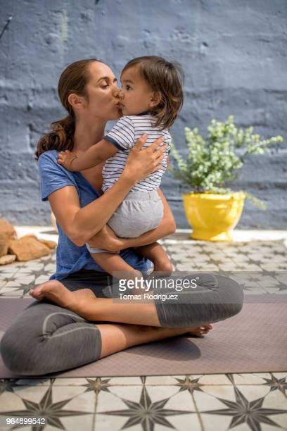 Woman on yoga mat kissing a toddler boy