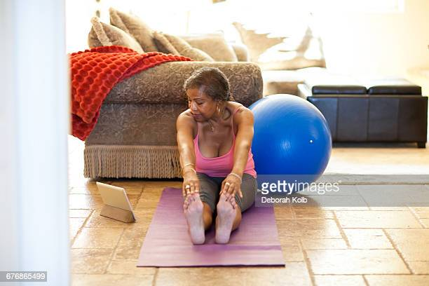 Woman on yoga mat using digital tablet, stretching