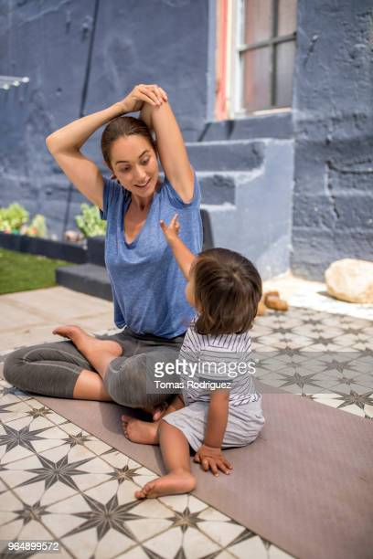 Woman on yoga mat with a toddler boy