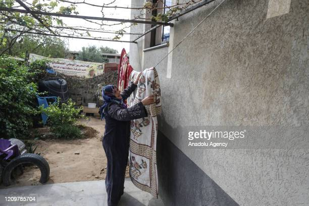 Woman, one of a family of eight, doing housework while spending time at home as a precaution against the coronavirus pandemic in Khan Yunis, Gaza on...
