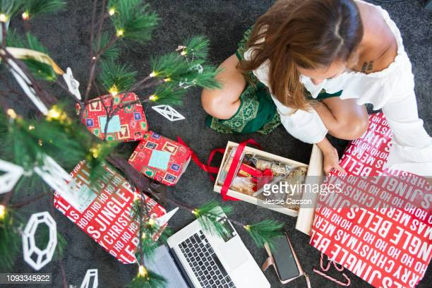 Woman online christmas shopping and wrapping presents
