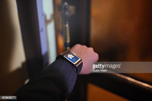 Woman open door with smartwatch.