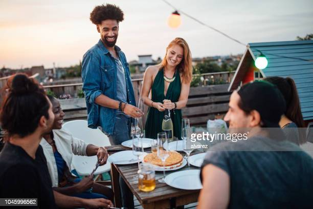 woman opening a champagne at rooftop party - barbecue social gathering stock pictures, royalty-free photos & images