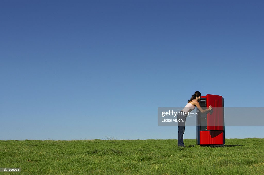 Woman Opening a Fridge Door and Standing Outdoors on Grass : Stock Photo