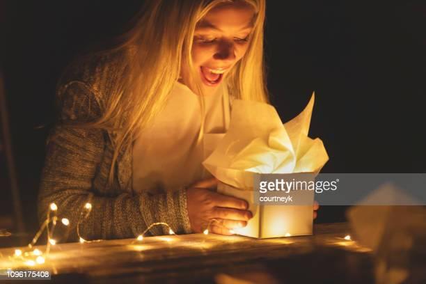 mujer abriendo una caja de regalo con un regalo dentro. su boca está abierta por la sorpresa. - aniversario fotografías e imágenes de stock