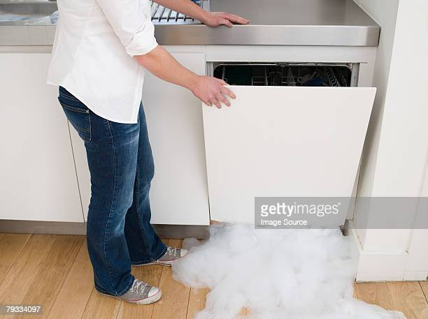 Woman opening a leaking dishwasher