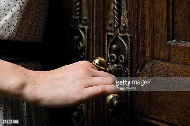 Woman opening a wooden door