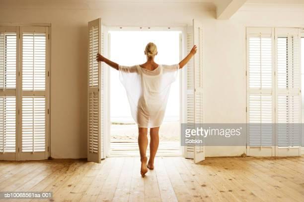 Woman opening beach house door