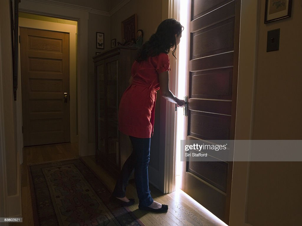 Woman opening bedroom door with light coming out : Stock Photo