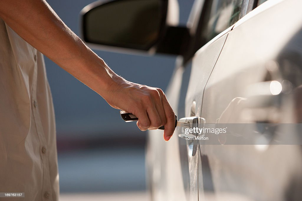 Woman opening car door : Stock Photo