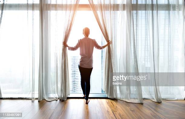 woman opening curtains and looking out - looking through window stock pictures, royalty-free photos & images