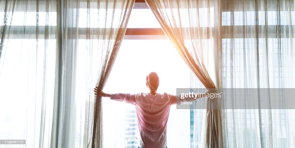 Woman opening curtains and looking out : Stock Photo