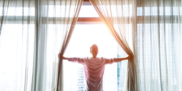 Woman opening curtains and looking out 1133497122
