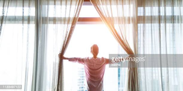 woman opening curtains and looking out - waking up stock pictures, royalty-free photos & images