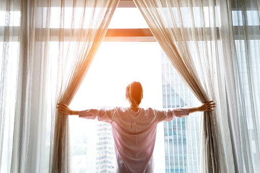 Woman opening curtains and looking out 948550464