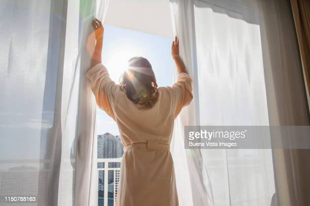 woman opening curtains - look back at early colour photography stock pictures, royalty-free photos & images